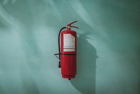 fire-extinguisher-on-green-wall